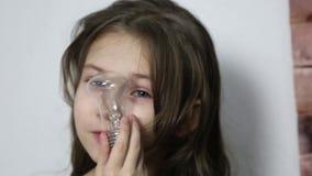 En flicka ser till och med en elektrisk lampa arkivfilmer