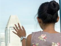 En flicka ser ut fönstret på skyskraporna Royaltyfri Foto