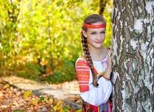 En flicka ser ut ur björkträd i höstskogen Arkivfoto