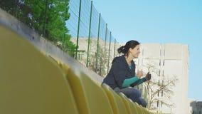 En flicka sitter i åskådarläktaren av stadion, 4k stock video