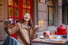 En flicka sitter i ett kafé, rymmer ett höstblad, skrattar och gör en selfiemobiltelefon Royaltyfri Bild