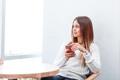 En flicka, sitter i ett kafé, rymmer en smartphone och ser ut fönstret arkivfoton