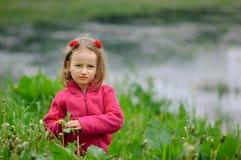 En flicka sitter i gräset på banken av en sjö, en flod Barnet ser allvarligt på linsen Koncentrerad blick Royaltyfria Foton
