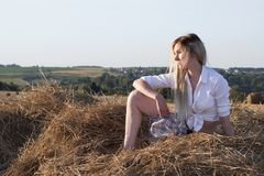 En flicka sitter i en höstack på bakgrunden av det lantliga landskapet royaltyfria bilder