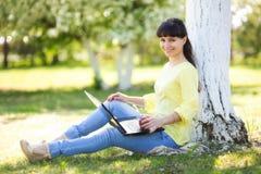 En flicka sitter med en bärbar dator nära ett träd arkivfoto