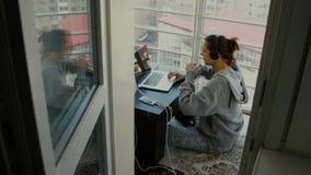 En flicka sitter på balkongen med en bärbar dator stock video