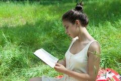 En flicka sitter på gräset och läser en bok royaltyfri foto