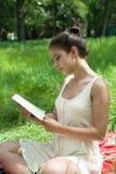 En flicka sitter på gräset och läser en bok fotografering för bildbyråer