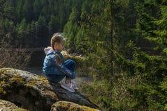 En flicka sitter på en klippa, och blickar på naturen, flickan som sitter på, vaggar och tycker om dalsikt arkivbild