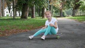 En flicka sitter på skateboarden och ritten från sida till sidan stock video
