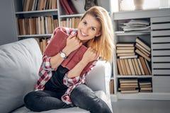 En flicka sitter på en soffa och läser en bok i en vardagsrum arkivbilder
