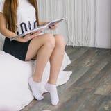 En flicka sitter på soffan och läsningen en tidskrift Han ser tidskriften Tidningen arkivbilder