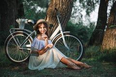 En flicka sitter under ett träd i gräset bredvid en cykel Royaltyfria Foton