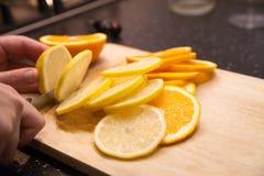 En flicka skär upp en citron Närbild arkivbilder