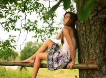 En flicka som drömmer under träd i lantligt ställe Arkivbilder