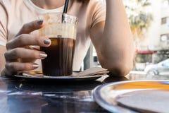 En flicka som dricker kallt kaffe, medan tala på den varma sommardagen royaltyfri bild