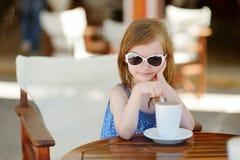 En flicka som dricker varm choklad i utomhus- kafé Fotografering för Bildbyråer