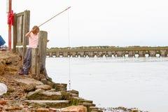 En flicka som fiskar för krabbor på banken av floden Blyth i Southwold, UK arkivfoto