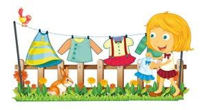 En flicka som hänger hennes kläder på trädgården Arkivfoton
