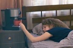 En flicka som inte kan vakna upp i morgonen utan en kopp kaffe Arkivfoto