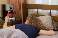En flicka som inte kan vakna upp i morgonen utan en kopp kaffe Royaltyfria Bilder