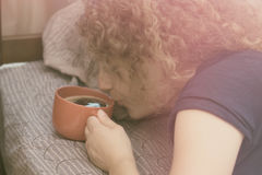 En flicka som inte kan vakna upp i morgonen utan en kopp kaffe Royaltyfri Bild