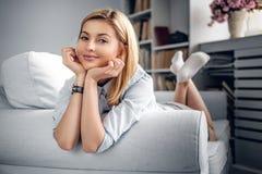 En flicka som kopplar av på en soffa i ett rum med bokställningar arkivbild