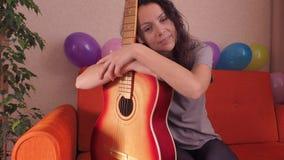 en flicka som leker på en akustisk gitarr stock video