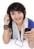En flicka som lyssnar till sånger från hennes mobiltelefon Royaltyfria Bilder