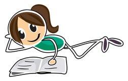 En flicka som ner ligger, medan läsa Arkivbild