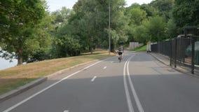 En flicka som rider en cykel i, parkerar, tidigt på morgonen arkivfilmer