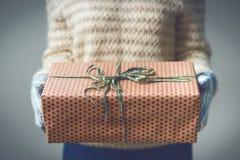 En flicka som rymmer en ask med en julklapp Royaltyfri Foto