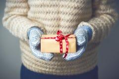 En flicka som rymmer en ask med en julklapp Royaltyfria Bilder