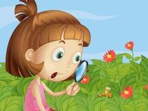 En flicka som rymmer en förstoringslins Arkivbild
