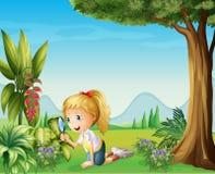 En flicka som rymmer en förstoringslins Royaltyfria Bilder