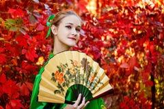 En flicka som rymmer en fan Royaltyfria Foton