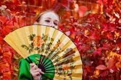 En flicka som rymmer en fan Royaltyfria Bilder