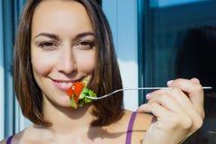 En flicka som rymmer en gaffel med grönsaker Arkivfoto