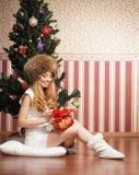 En flicka som rymmer ett aktuellt near en julgran royaltyfri bild