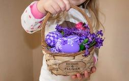 En flicka som rymmer en korg med målade ägg och blommor i lila blommor, för påsk arkivfoton