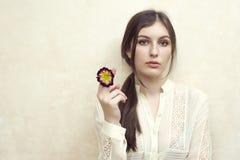 En flicka som rymmer primeroseblomman som låtsar att röka fotografering för bildbyråer