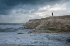 En flicka som ser det stormiga havet Arkivbilder