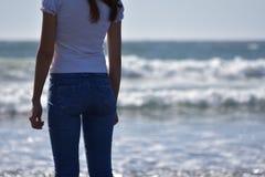 En flicka som ser en solnedgång i en strand royaltyfria foton