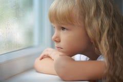 En flicka som ser ut ur fönstret på en regnig dag arkivfoton