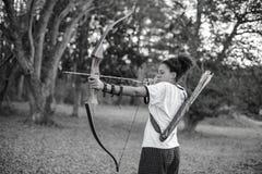 En flicka som siktar pilbågen och pilen i skogen royaltyfri fotografi