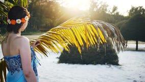 En flicka som slår en torkad palmträd lager videofilmer