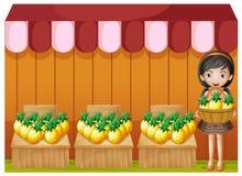 En flicka som säljer ananors Arkivbild