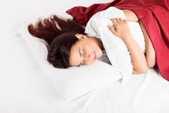 En flicka som sover på en säng som kramar en kudde Arkivfoto