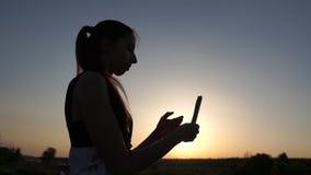 En flicka som spricker ut sedlarna på solnedgången i ultrarapid, hennes kontur, är synlig arkivfilmer