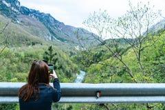 En flicka som står på klippan och tar fotografiet av dalen med floden Rött huvud som gör bilden med den smarta telefonen till Tar fotografering för bildbyråer